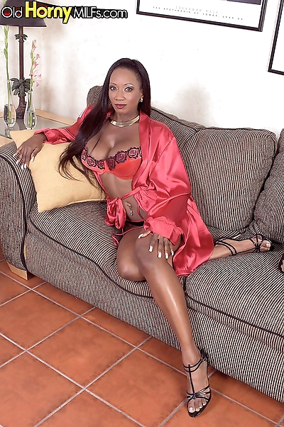 Busty black lady toys her..