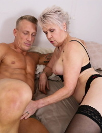 Horny granny kissing her young jock plaything before getting his hard cock